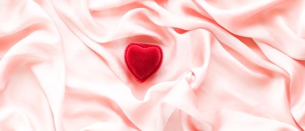 Pudełko na biżuterię w kształcie czerwonego serca na różowym jedwabnym walentynki koncepcja prawdziwej miłości i propozycji, czy będziesz moją walentynką