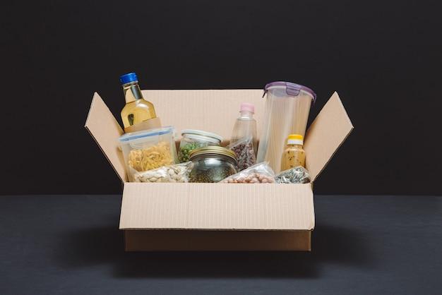 Pudełko na darowizny z różnymi artykułami spożywczymi. otwórz kartonowe pudełko z olejem, konserwami, płatkami zbożowymi i makaronem.