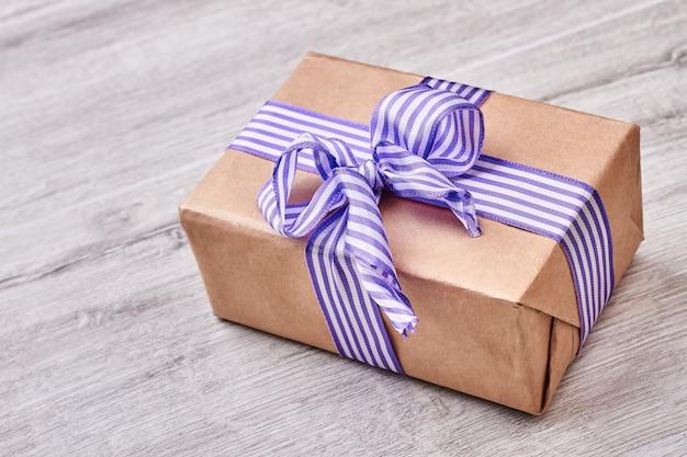 Pudełko na drewnianym tle. kokarda w paski na prezent.