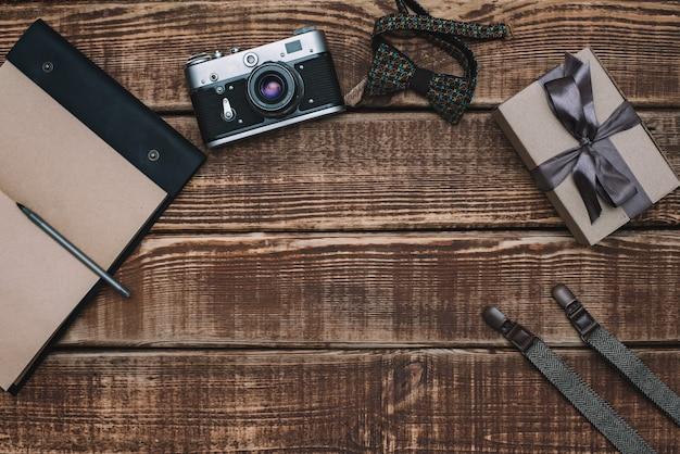 Pudełko na dzień ojca z muszką, portfelem, aparatem retro, szelkami i notatnikiem oraz skórzanymi butami na drewnianym stole. leżał płasko.