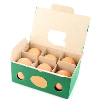 Pudełko na jajka z sześcioma brązowymi jajami na białym tle na białej powierzchni