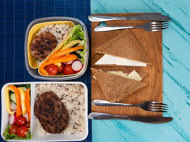 Pudełko na lunch z apetycznym jedzeniem i na jasnym drewnianym stole. skopiuj miejsce.