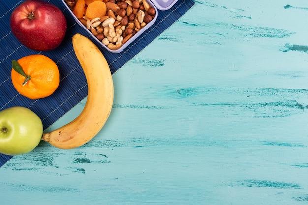 Pudełko na lunch z apetycznym jedzeniem i na jasnym drewnianym stole