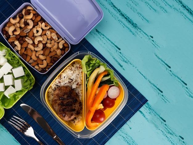Pudełko na lunch z apetycznym jedzeniem i na jasnym drewnianym stole.