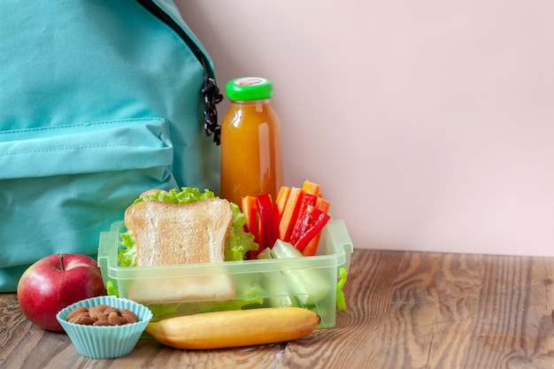 Pudełko na lunch z apetycznym jedzeniem i plecakiem na drewnianym stole.