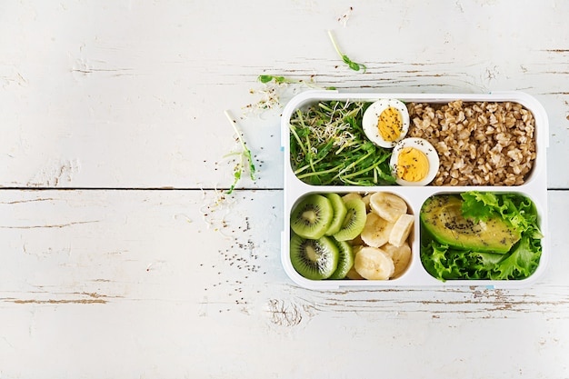 Pudełko na lunch z gotowanymi jajkami, płatkami owsianymi, awokado, mikro zieleniną i owocami. zdrowa żywność fitness. na wynos. pudełko śniadaniowe. widok z góry