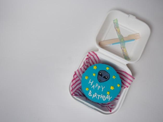 Pudełko na lunch z koreańskim ciastem, tort z napisem happy birthday i twarzą kosmity. miejsce na twój tekst