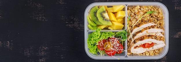 Pudełko na lunch z kurczakiem, bulgur, mikrogreenami, pomidorem i owocami.