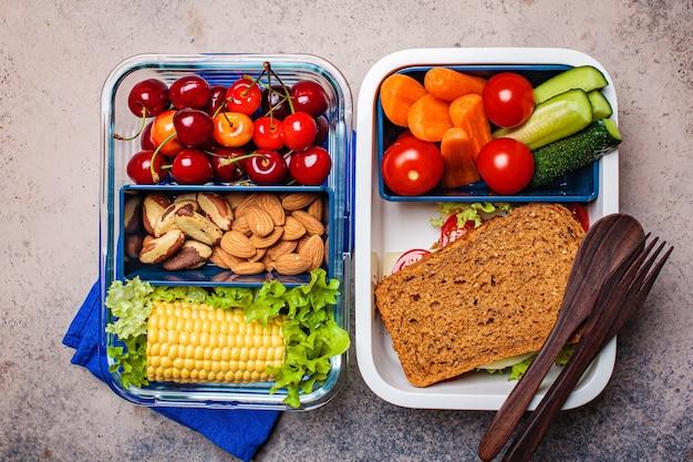 Pudełko na lunch ze zdrową, świeżą żywnością. kanapka, warzywa, owoce i orzechy w pojemnikach na żywność, ciemne tło.
