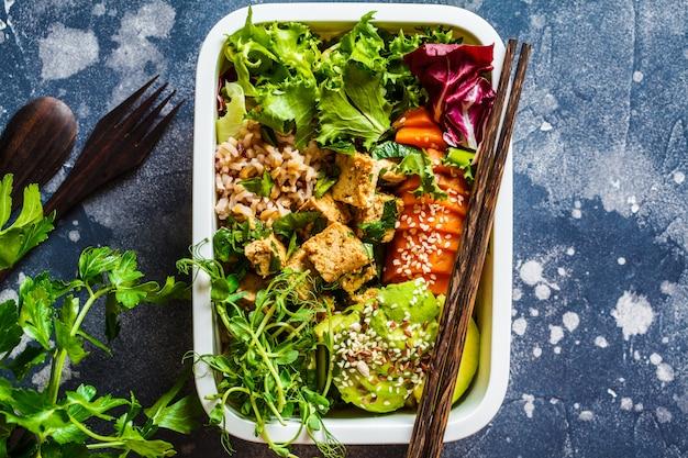 Pudełko na lunch ze zdrowym wegańskim jedzeniem. pudełko bento z ryżem, słodkimi ziemniakami, tofu i warzywami.