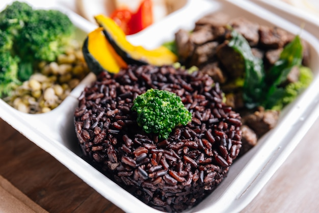 Pudełko na mączkę z żywnością: grillowana wołowina z grilla podana z jagodami ryżowymi i grillowanymi warzywami.