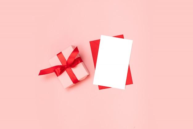 Pudełko na niespodziankę owinięte w różowy papier z czerwoną kokardą, pusty czerwony szablon koperty na różowym tle