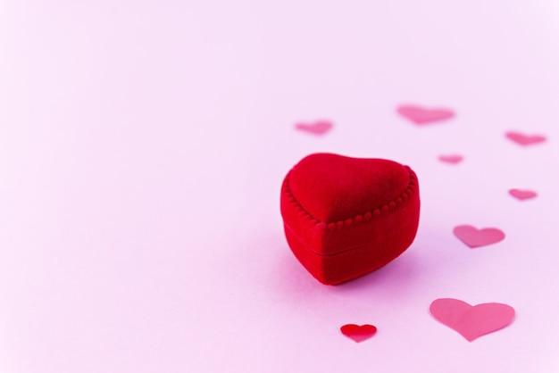 Pudełko na pierścionek w kształcie serca na różowym tle.