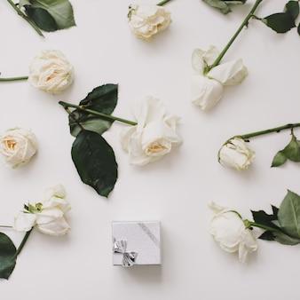 Pudełko na pierścionek z biżuterią i białe róże na białym tle