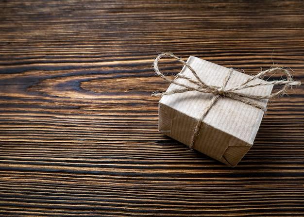 Pudełko na prezent craft wiązane liną jutową na brązowym starym drewnianym tle