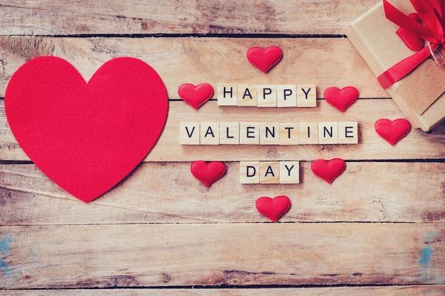 Pudełko na prezent i czerwone serce z drewnianym tekstem happy valentine day na tle drewna tabeli.