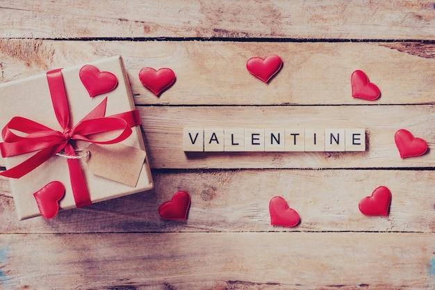 Pudełko na prezent i czerwone serce z drewnianym tekstem valentine na tle drewna stół.