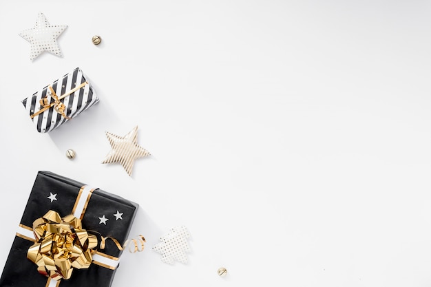 Pudełko na prezent lub prezent, czapeczki i gwiazdy na białym stole. kompozycja świąteczna z czarnymi i złotymi zdobieniami
