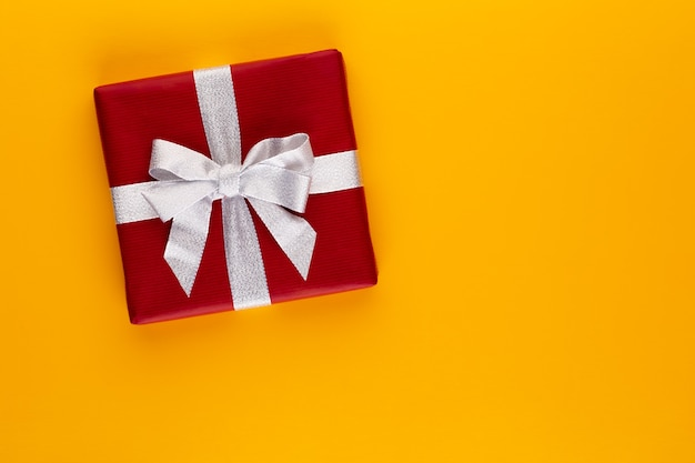 Pudełko na prezent lub prezent na kolorowym widoku z góry. płaska kompozycja świeckich na urodziny, dzień matki lub wesele.