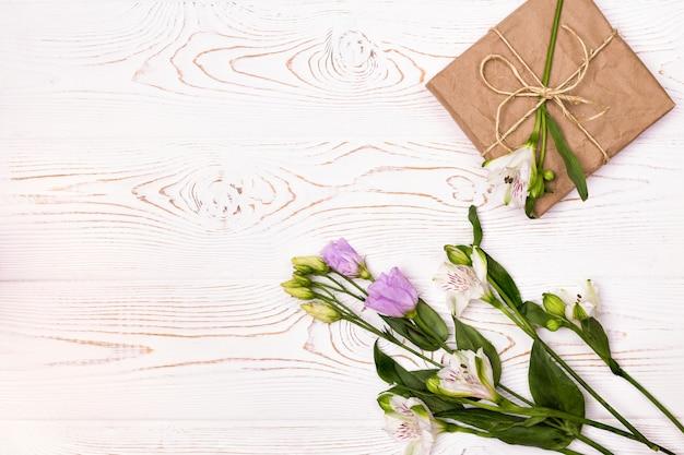 Pudełko na prezent lub prezent zawinięte w papier pakowy i kwiat na białym stole z góry płaskie miejsce na kopię