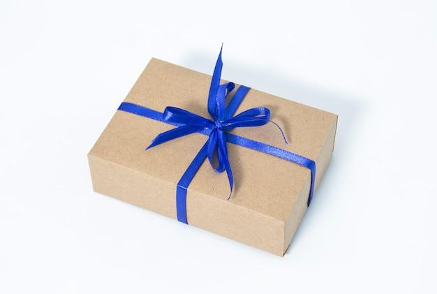 Pudełko na prezent owinięte w papier kraft wiązany świąteczną liną z trzciny cukrowej na ciemnoniebieskim tle
