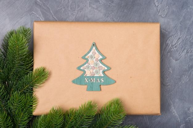 Pudełko na prezent świąteczny w papierze rzemieślniczym z wystrojem z drzewa drewnianego na ciemnym tle z futrem. noworoczna koncepcja x-mas.