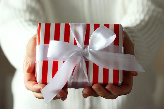 Pudełko na prezent w kobiece ręce daje prezent
