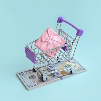 Pudełko na prezent w małym koszyku leży na banknotach dolarowych o