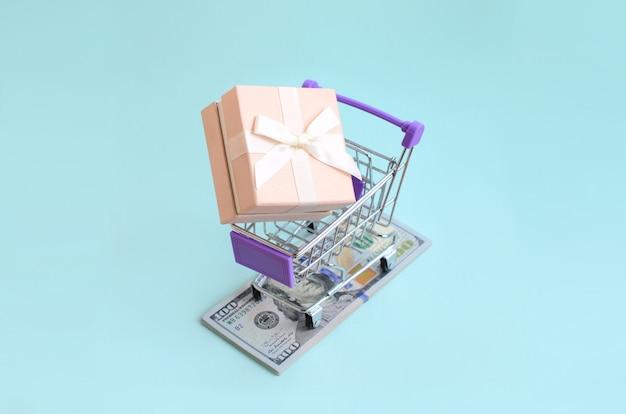 Pudełko na prezent w małym koszyku leży na banknotach dolarowych