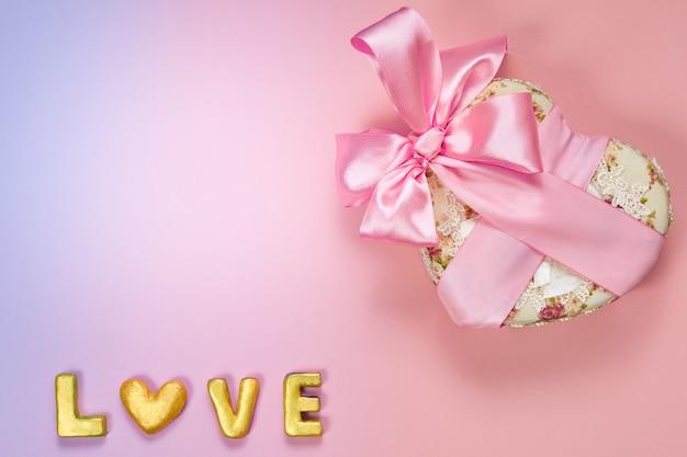 Pudełko na prezent walentynki w kształcie serca z różową zakrzywioną wstążką i złotym słowem miłość na tle papieru.