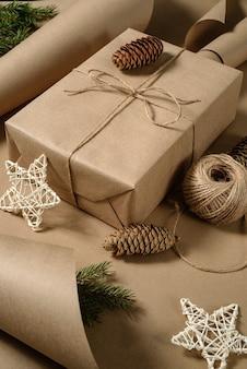 Pudełko na prezent zawinięte w brązowy papier pakowy i przewiązane sznurem.