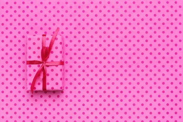 Pudełko na różowym papierze pakowym w kropki.