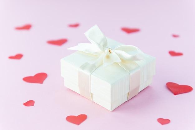 Pudełko na różowym tle z czerwonym sercem na walentynki.