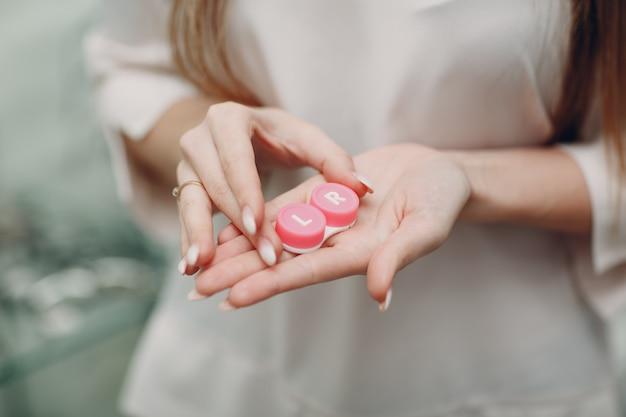 Pudełko na soczewki kontaktowe. kobieta trzyma się za ręce etui na soczewki
