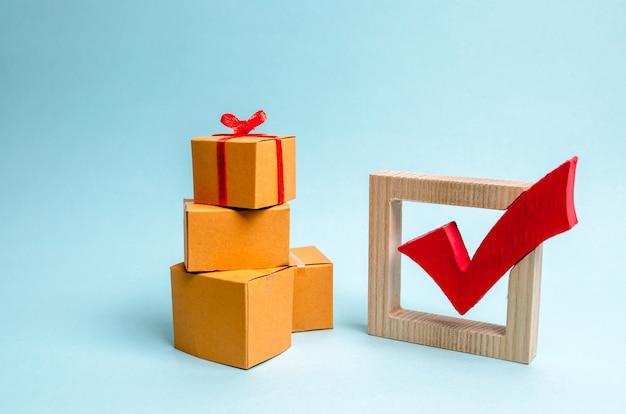 Pudełko na stos pudeł i czerwony znacznik wyboru. koncepcja znalezienia idealnego prezentu.