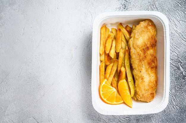 Pudełko na wynos danie z rybą z frytkami i frytkami. białe tło. widok z góry. skopiuj miejsce.