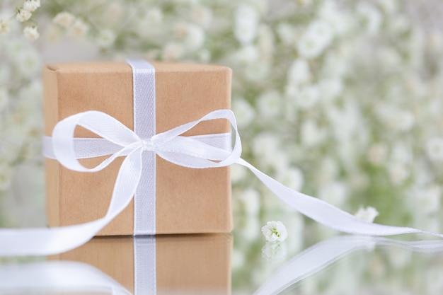 Pudełko owinięte w brązowy papier z białymi kwiatami łyszczecowej paniculata. kartka z życzeniami.