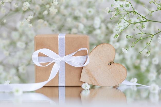 Pudełko owinięte w brązowy papier z drewnianym sercem i białymi kwiatami gipsówki paniculata. kartka z życzeniami.