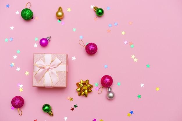 Pudełko owinięte wstążką, ozdobnymi kulkami i płatkiem śniegu na kolorowym różowym tle papieru z cukierkami w kształcie gwiazdek. prezent na boże narodzenie. koncepcja wakacje. obraz z miejsca na kopię. płaski widok z góry
