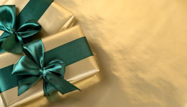 Pudełko owinięte złotym papierem z zieloną satynową wstążką