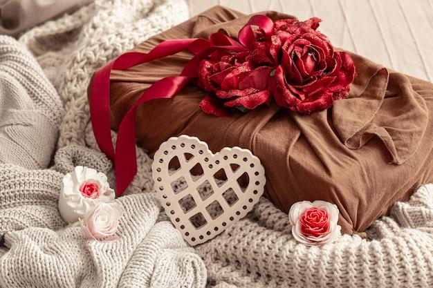 Pudełko ozdobione wstążkami i ozdobnymi różyczkami na dzianinach. oryginalne opakowanie na prezent na walentynki.