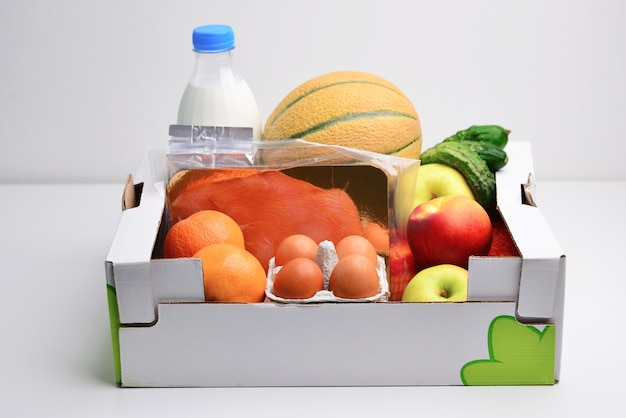 Pudełko pełne jedzenia w koncepcji darowizny na białym tle
