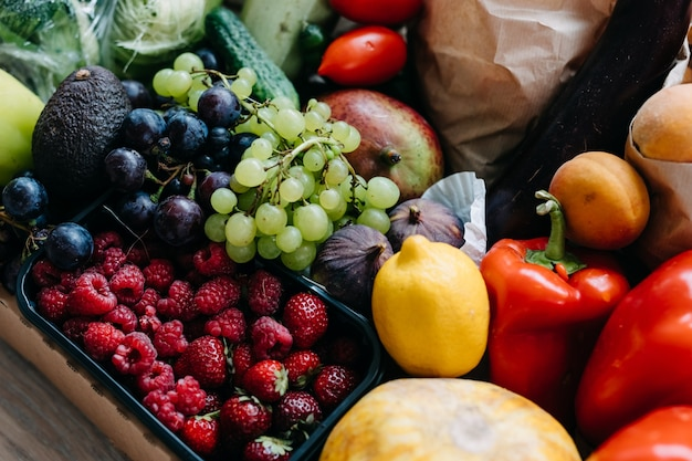 Pudełko pełne różnych organicznych jagód, warzyw i owoców koncepcja dostawy żywności