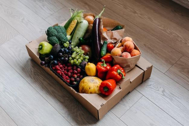 Pudełko pełne różnych organicznych warzyw, owoców i jagód na podłodze koncepcja dostawy żywności
