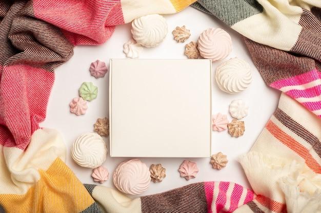 Pudełko, piękny szalik, bezy i słodycze na jasnym tle. kompozycja walentynki. transparent. widok płaski, widok z góry.