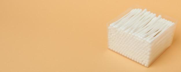 Pudełko plastikowe z wacikami na beżowym tle