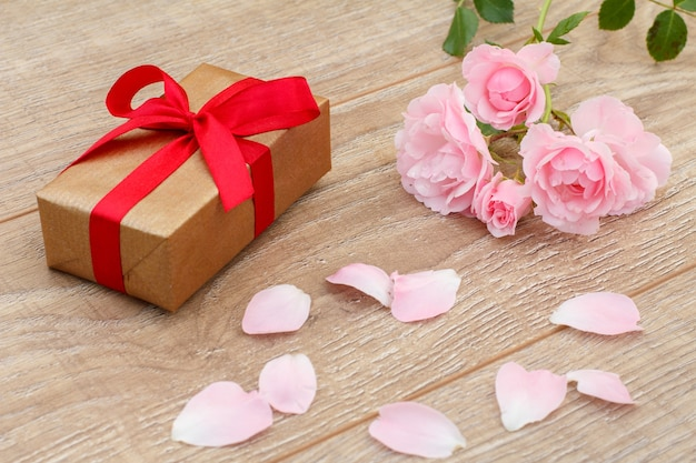 Pudełko, płatki róż i piękne różowe róże na drewnianym tle. koncepcja dawania prezentu na święta. widok z góry.