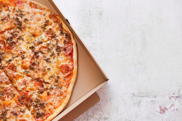 Pudełko po pizzy na biały kamień tekstury, z miejscem na tekst. fast food.