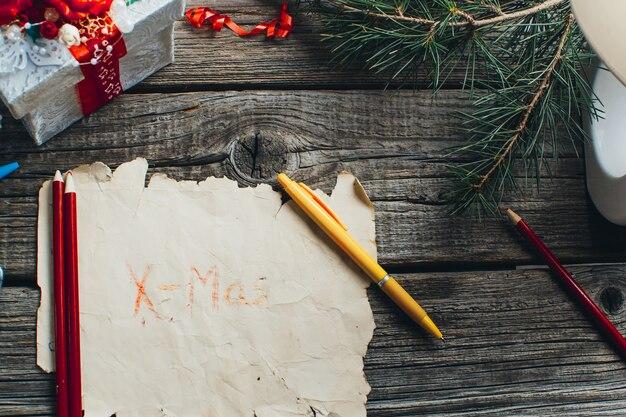 Pudełko prezentowe, brązowy, brązowy papier, żółty długopis na drewnianym stole, podpis boże narodzenie i nowy rok.