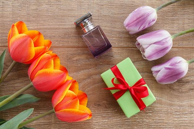 Pudełko prezentowe, butelka perfum z czerwonymi i liliowymi tulipanami na drewnianych deskach